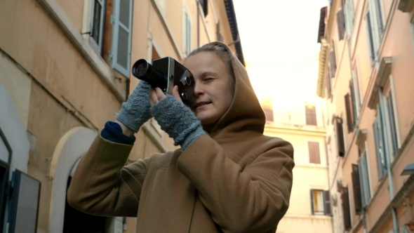 Woman Using Retro Video Camera In The Street
