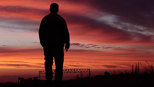 VideoHive Lonely Man Goes Along The Road Against Sunset 11990554