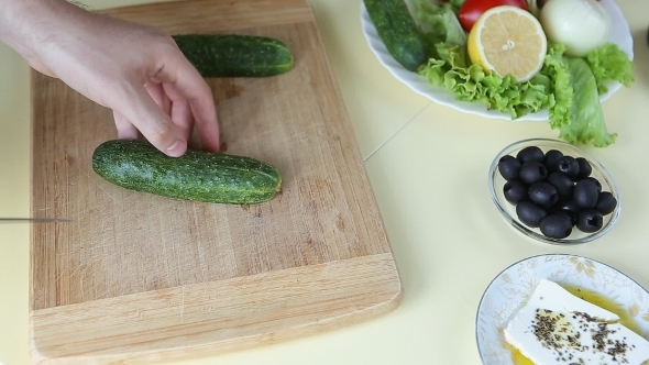 Hand Cutting Cucumber On Cutting Board With Sharp