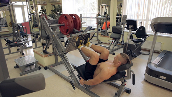 Bodybuilder Pushing Weights With Legs