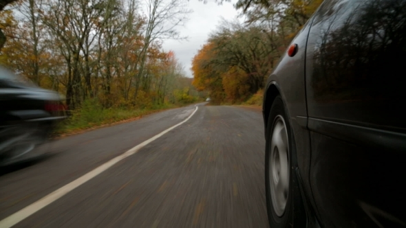 Passenger Car Moving Along Winding Road In Autumn