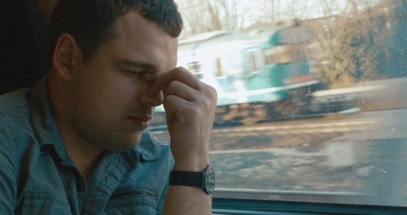 Man Taking a Headache Pill In The Train