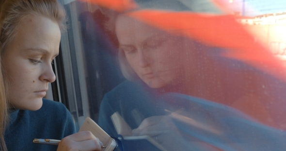 Woman Taking Notes Or Drawing In Train