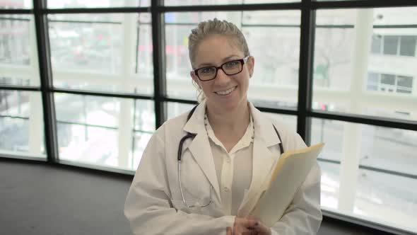 A Blonde Caucasian Female Medical Professional Walks Up To The Camera 2 Of 4