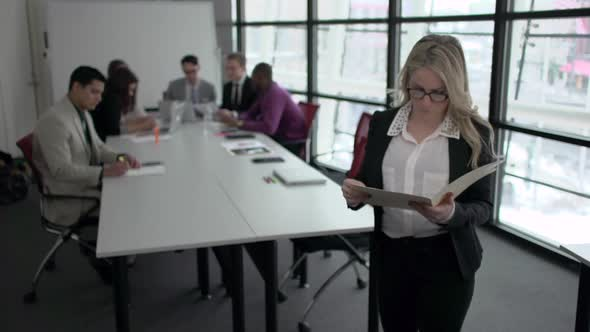 A Blonde Caucasian Woman Stands Infront Of Professionals In A Meeting 1 Of 5