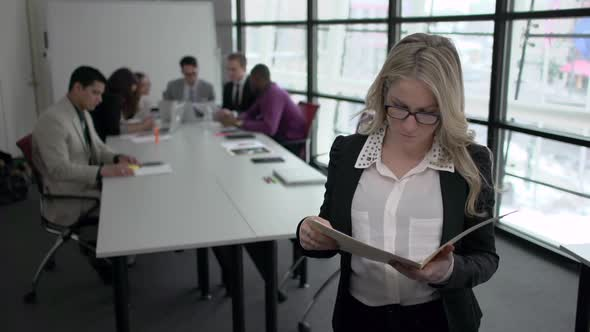 A Blonde Caucasian Woman Stands Infront Of Professionals In A Meeting 2 Of 5