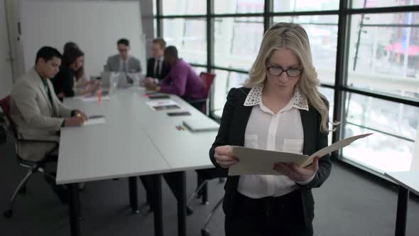 A Blonde Caucasian Woman Stands Infront Of Professionals In A Meeting 5 Of 5