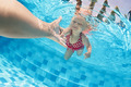 Child swimming underwater in the pool with parents