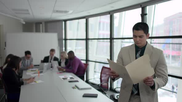 A Hispanic Man Stands Infront Of Professionals In A Meeting 6 Of 6