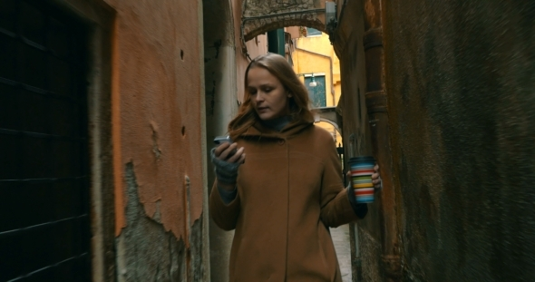 Woman With Phone And Coffee Walking In Venice