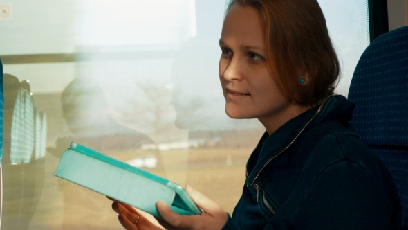 Woman Chatting On Tablet PC In Train
