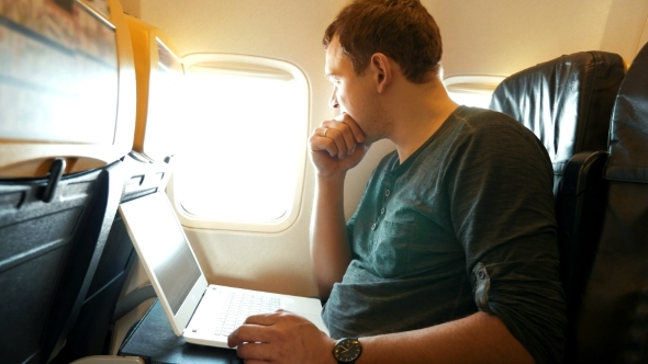 Young Man Chatting On Laptop In The Plane