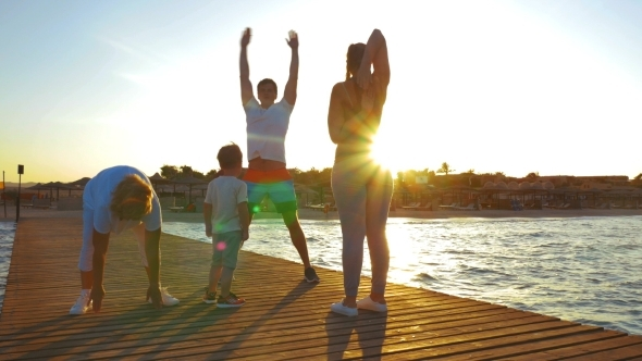 Family Exercising On The Pier At Sunset