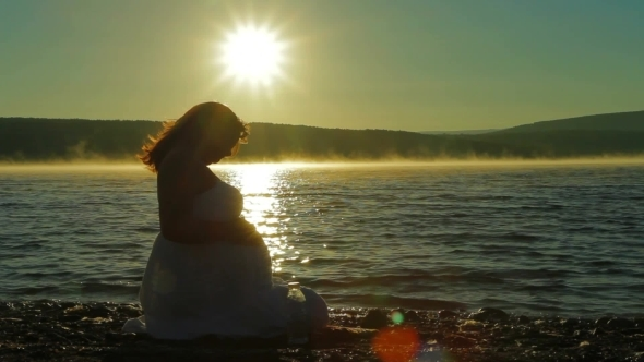 Pregnant Sits On The Lake In The Early Morning And