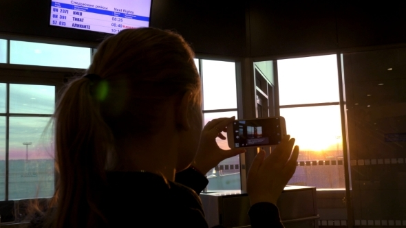 Woman Making Sunset Photos With Cell