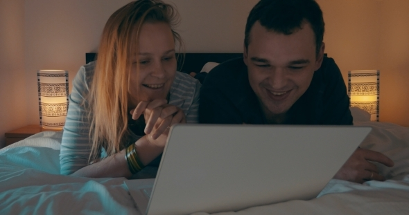 Couple In Bed Watching Movie On Laptop