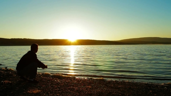 VideoHive A Man Throwing Pebbles Into Water 12039592