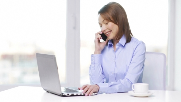 Businesswoman With Laptop And Smartphone At Office