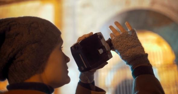 Tourist Using Retro Camera To Shoot Night Coliseum