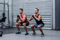 Squatting muscular men exercising with kettlebells
