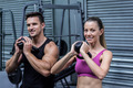 Portrait of a muscular couple exercising with kettlebells