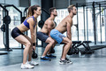 Side view of three muscular athletes squatting with kettlebells