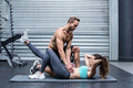 Muscular couple doing abdominal exercises at the crossfit gym