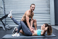 Portrait of a muscular couple doing abdominal exercises