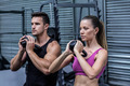 Side view a muscular couple exercising with kettlebells
