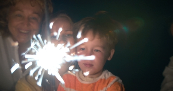Parents Child And Sparkler At Night
