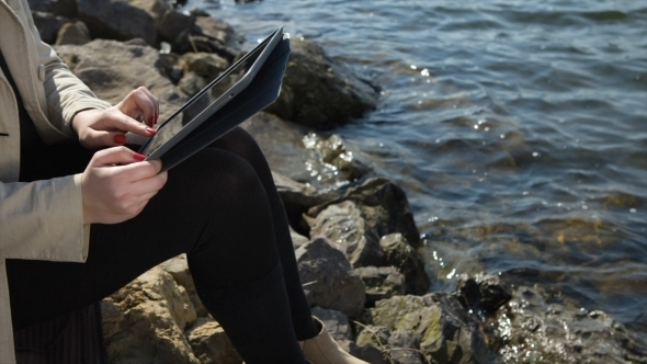 Beautiful Girl Working On Tablet At The Beach