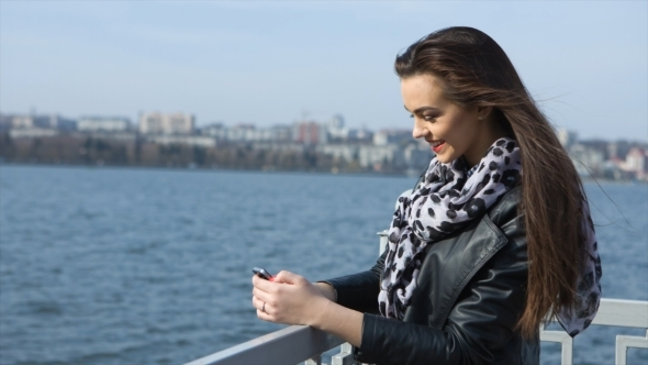 Beautiful Girl With Phone On a Background Of Water