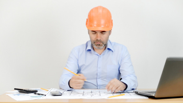 Engineer Working in Office on Blueprint