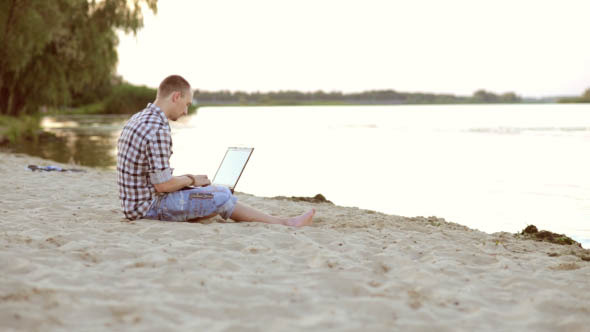Man Resting a Laptop on the Beach