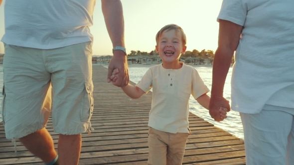 Happy Boy Walking With Grandparents Along The Pier