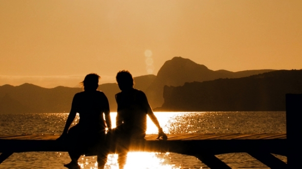 Young Couple Sitting On Bridge At Sunset