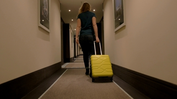 Woman Walking Along The Hotel Passage With Trolley