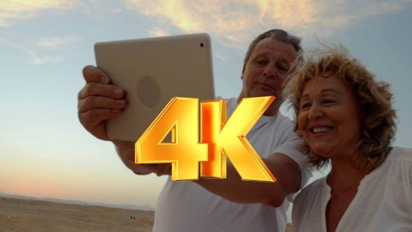 VideoHive Senior Couple Using Touch Pad Outdoor On Vacation 12157688