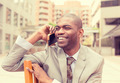 handsome happy young businessman talking on mobile phone