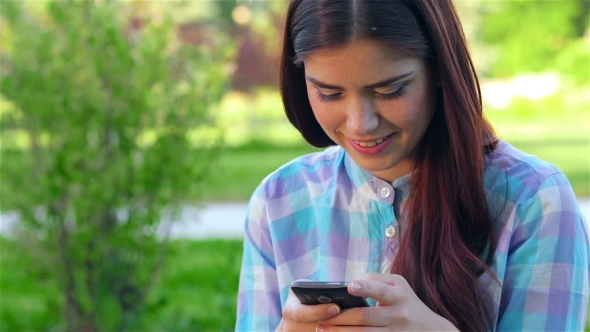 VideoHive Beautiful Smiling Young Woman Using Mobile In Park 12164002