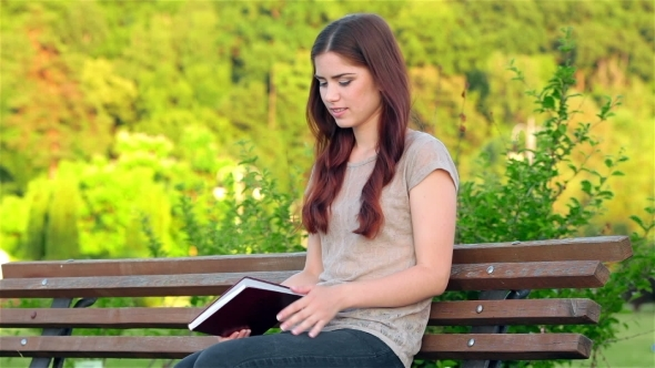 VideoHive Attractive Girl With a Diary Sitting On The Bench 12164175