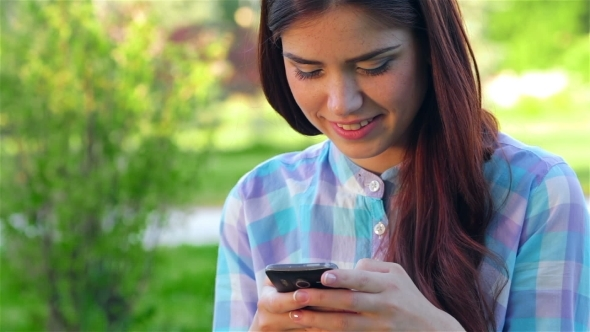 VideoHive Beautiful Smiling Young Woman Using Mobile In Park 12164192