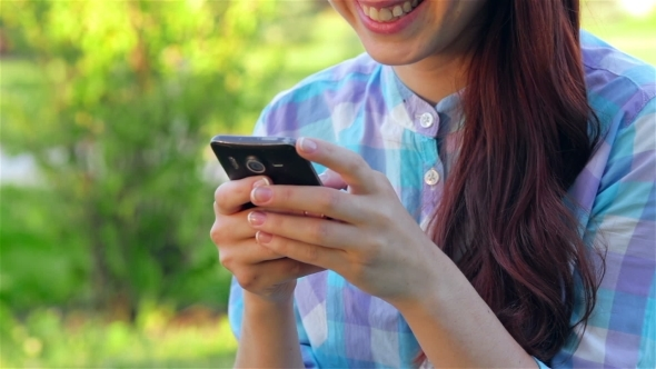 VideoHive Beautiful Smiling Young Woman Using Mobile In Park 12164311