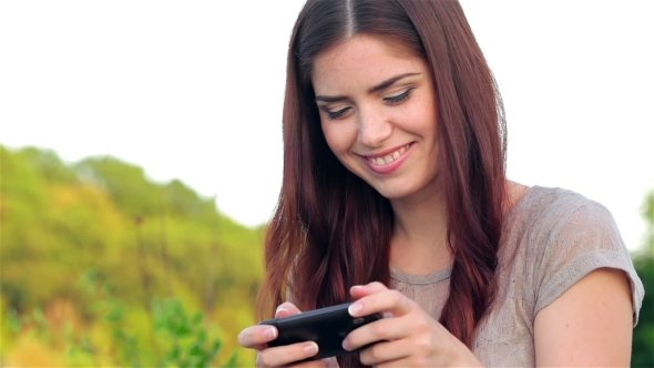 VideoHive Young Woman In Park Texting On The Phone 12164333