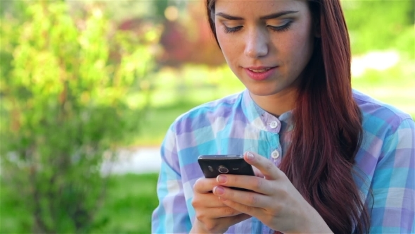 VideoHive Beautiful Smiling Young Woman Using Mobile In Park 12164353