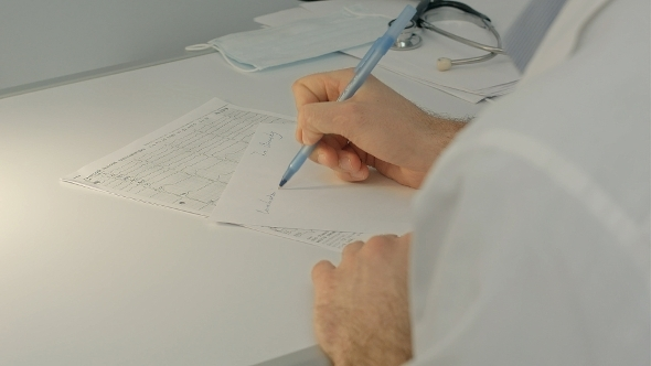 VideoHive Doctor Sitting On The Desk With Paper And Working 12172626