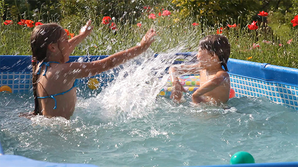 VideoHive Kids Have Fun Swimming in a Pool 12175355