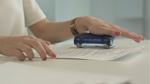 VideoHive Woman Using a Hole Puncher 12186921
