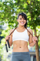Portrait of smiling athletic woman with skipping rope looking at camera in the city