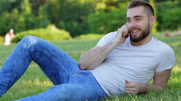 VideoHive Handsome Man On The Grass With Phone 12221240